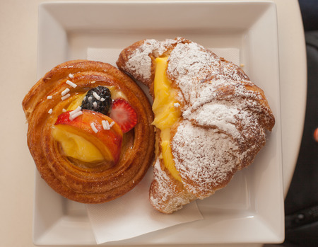 velo: Cake with fruit and a croissant with cream on a plate close-up.