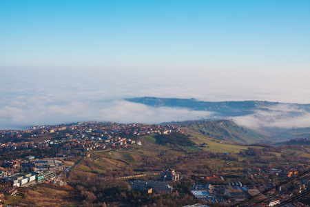 shrouded: Panorama of rolling countryside with the city shrouded in mist. The valley and the city in the mist. Stock Photo