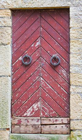 puertas de hierro: Puerta de madera vieja con la ronda maneja el hierro y la pintura descascarada.