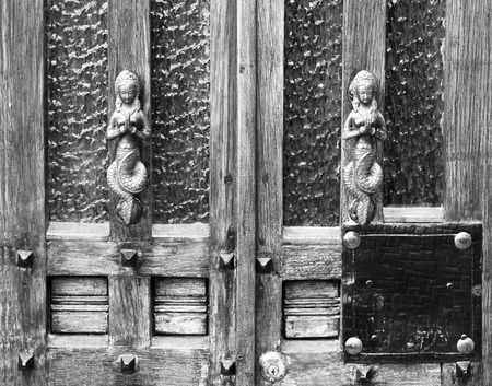 and gate: Vintage silver door handles in the form of a mermaid - background.