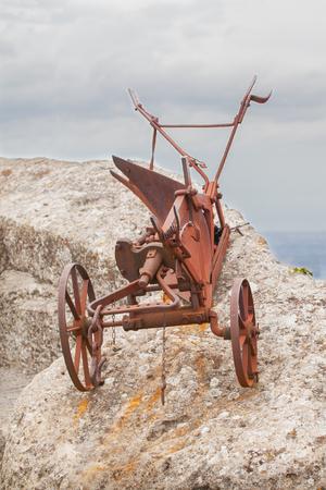 ironmongery: Que no funciona el arado viejo oxidado en un acantilado como una pieza de museo. Foto de archivo