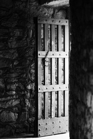 entrance gate: The open old wooden door in the tower, the view from the inside. Stock Photo