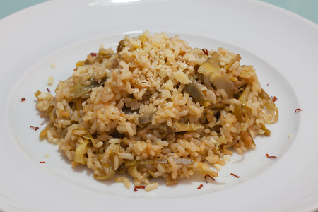 queso rayado: Brown rice with carciofi and grated cheese on the plate close-up.