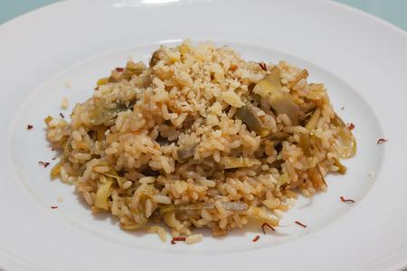 queso rallado: El arroz integral con carciofi y el queso rallado en la placa de primer plano.