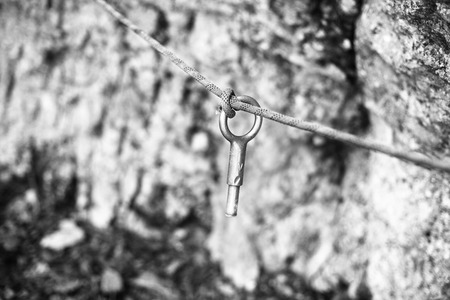 belaying: Mountaineering fixing ring with a rope fixed on the mountain.
