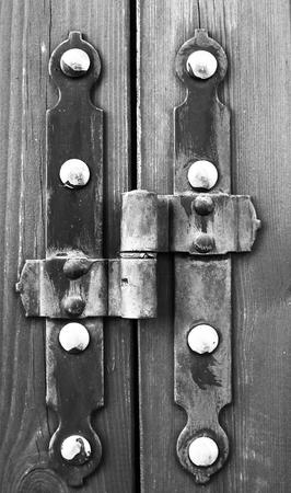 hinge: Old door hinge on cracked wooden door.