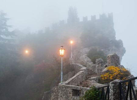 Ancient stone stairs leading to the fortress wall in the fog.