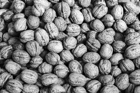 Pile of walnuts in shells,walnut background.Lots of walnuts closeup Stock Photo