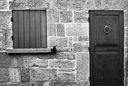 Stone wall of old building with wooden vintage door and windows. Stock Photo