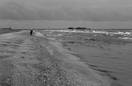 Lonely figure in the autumn on the beach on a cloudy day.