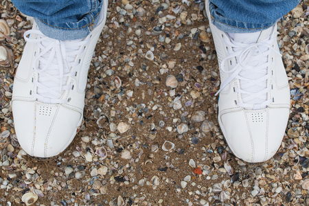 Men's feet in sneakers on the sand among the many shells.