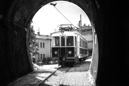Old tram on the background of the entry to the tunnel on the city street.