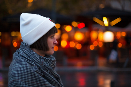 Girl in profile in the street in the evening in the light of night lights. Bokeh background.