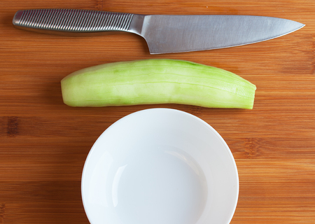 Cucumber, plate and knife on a cutting board close-up.