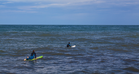Two surfers in the water waiting for the wave.
