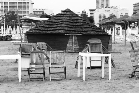 Wooden house with a reed roof on the beach.