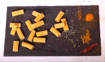 Raw macaroni close-up on a black background. Reklamní fotografie