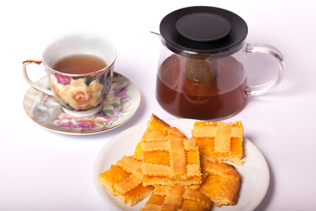 Crostata with apricot jam and a cup of tea on a white background.