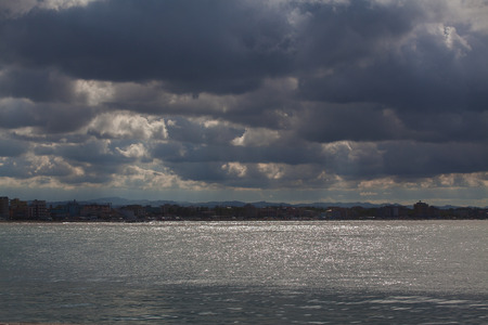 View from the sea to the coastline on a cloudy day. The sky with clouds