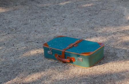 Green old suitcase on grass close-up. Reklamní fotografie