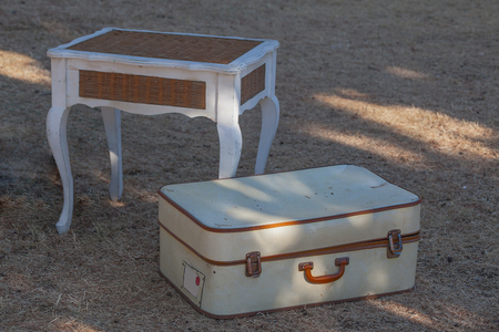 Old white suitcase on the grass and a wicker table close-up. Reklamní fotografie