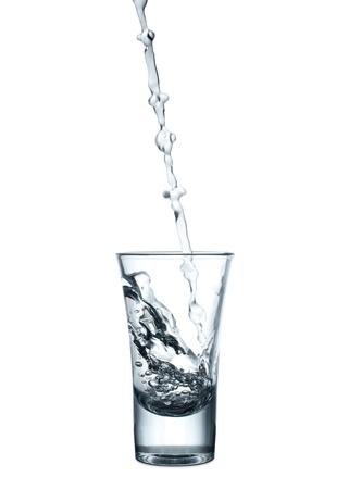 vasos de agua: Verter agua en un vaso sobre fondo blanco