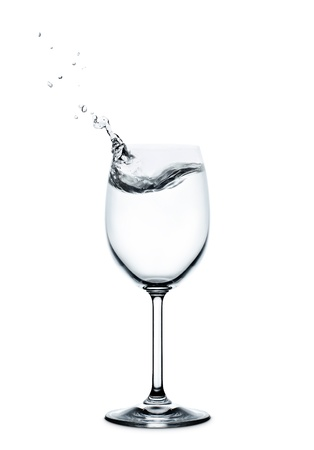splashing water wave in the wine glass on white background photo