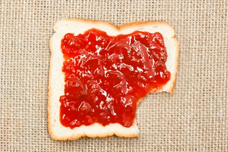missing bite: bite out of a slice of bread with strawberry jam on sacking background
