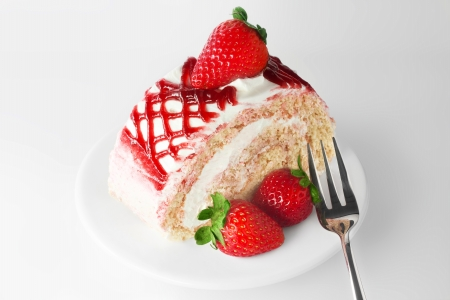 Fresh and sweet strawberry cake on white plate with fork photo