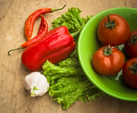 Healthy fresh vegetables ingredients for cooking in rustic setting: tomatoes, garlic, spices, chili. pepper photo