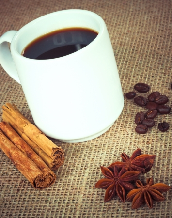 Coffee cup with cinnamon, anise and beans on sack photo
