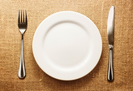 dinnerware: Photo of the fork and knife with white plate on sacking background Stock Photo