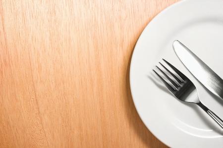 cuchillo: Foto del tenedor y cuchillo con placa blanca en el fondo de madera Foto de archivo