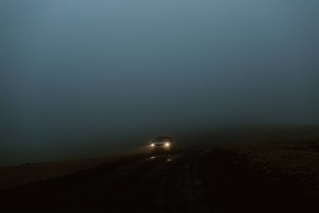 headlights of a car approaching in the dark, fog