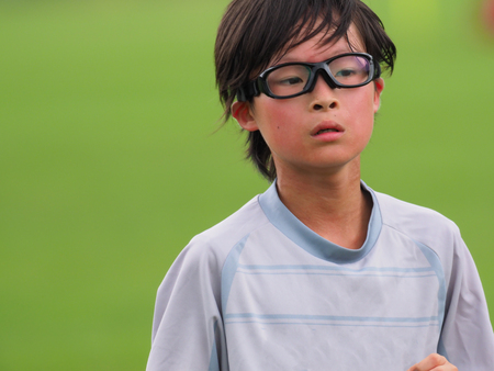 Kid playing soccer in the field Stock Photo