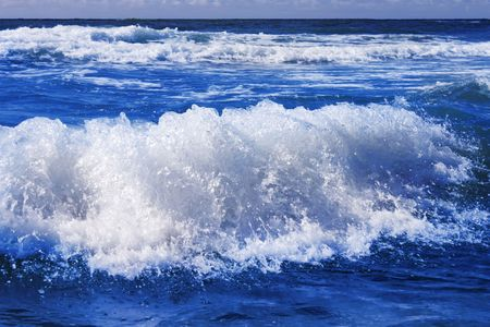 waves and surf at beautiful beach with blue water