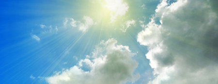 Rays of streaming sunlight on cloudy blue sky background. Summer, holiday, fun, banner, nature, concept.
