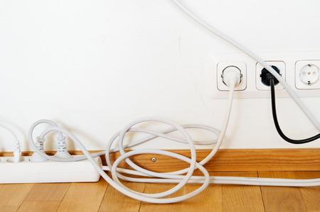 Toma de corriente múltiple y enchufes conectados a la toma de corriente en la pared. Foto de archivo