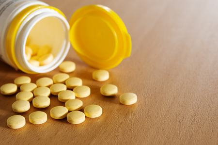Yellow pills on the wooden table.