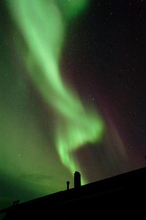 Aurora borealis above house roof and chimney Stock Photo
