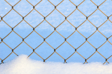 Detail of galvanized chain link fence in snow. Cold winter day. Stock Photo