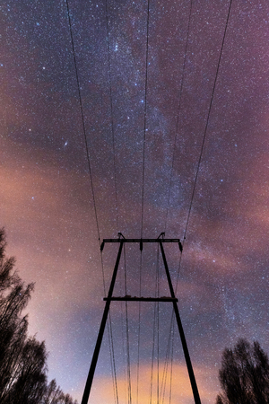 Power line under Milky Way and starry sky.