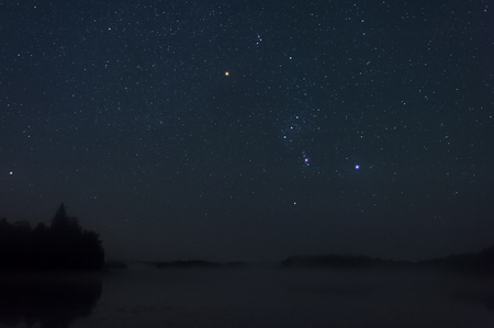 Orion constellation above misty lake