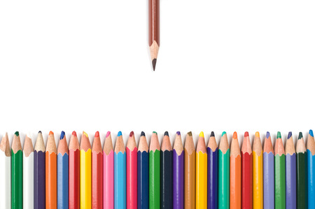 Colored pencils in a row on white background.