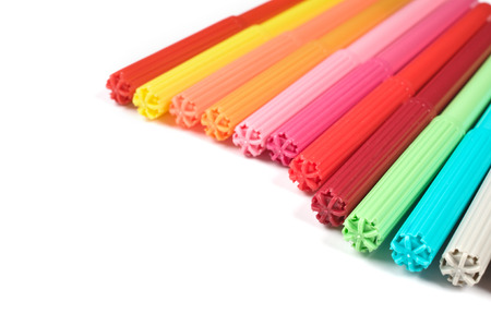 Colored felt tip pens in a row on white background.