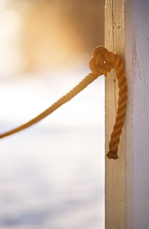 Rope knotted in to the pole. Focus on knot.