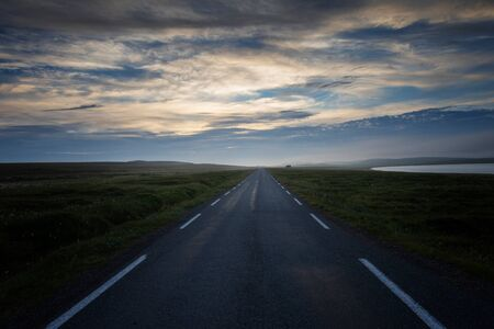 Country road across the tundra landscape in summer night. Finnmark, Norway