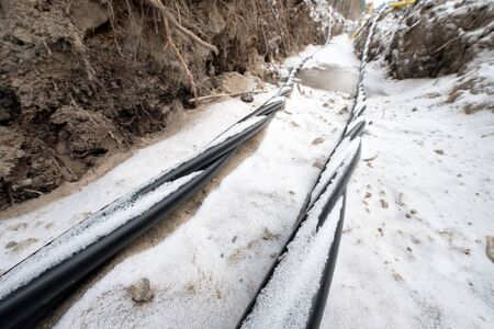 Laying a fiber optic and electricity cables in the frozen ground, buried cables for fast internet in rural region - underground cabling in Finland Banco de Imagens