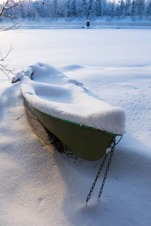 Rowboat lie in snow on the shore of an ice-covered frozen river in winter, Eastern Finland.