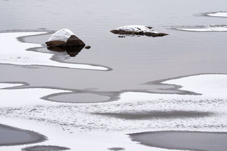 River begins to freeze, rocks poking out of the shallow water